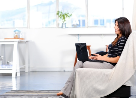online banking: Pretty woman connects to the internet wirelessly, shopping online from the comforts of her home  Stock Photo