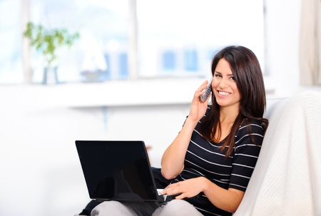 Beautiful woman at home surfing the internet and talking on the phone Stock Photo - 10803014
