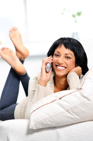 cordless: Attractive indian woman at home, lying on the couch with a telephone
