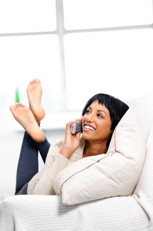 cordless: Smiling, carefree brunette relaxing on the couch, holding a telephone  Stock Photo
