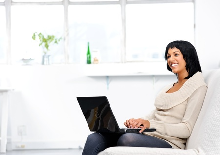 Indian woman sitting on the couch, typing on her laptop while thinking about her work Stock Photo - 10861495