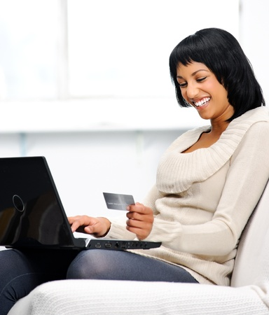 Smiling indian woman with laptop and credit card at home  photo