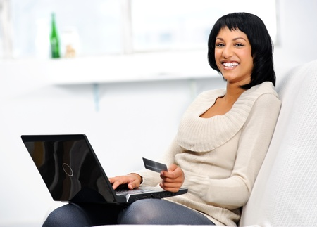 Smiling indian woman with laptop and credit card at home  Stock Photo - 10861476
