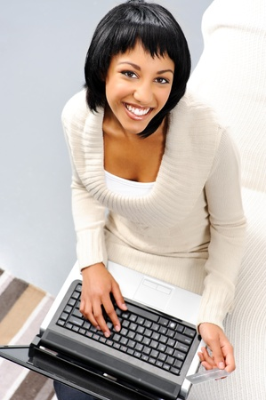 Top down perspective of a cute indian woman holding a credit card and typing on a laptop Stock Photo - 10861431