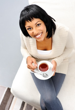 contented: Happy smiling woman holds a hot cup of tea to warm herself in winter  Stock Photo