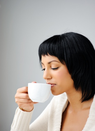 Attractive brunette enjoys her cup of tea before she goes to work  photo
