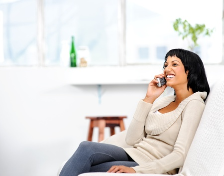 cordless: Young attractive woman sitting on the couch at home, chatting on the telephone