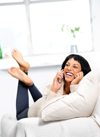 cordless: Cute indian girl laughing on the couch while on the telephone