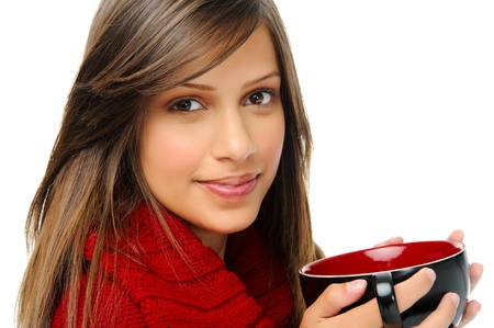 eurasian: attractive young woman holds a soup bowl and wears a red cardigan in winter