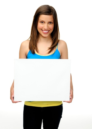 people holding sign: young woman holds a blank board providing copyspace for any advertising. friendly, approachable and smiling
