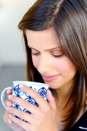 relaxed woman has a cup of tea at home photo
