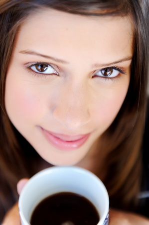 women holding cup: relaxed woman has a cup of tea at home