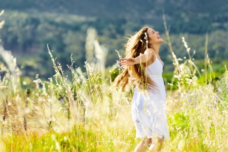meadow: beautiful girl laughs and dances outdoors in a meadow durning sunset