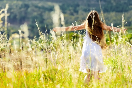 beautiful girl laughs and dances outdoors in a meadow durning sunset photo