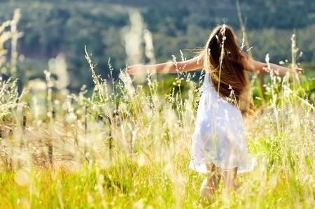 risas hermosa niña al aire libre y bailes en una puesta de sol prado durning Foto de archivo