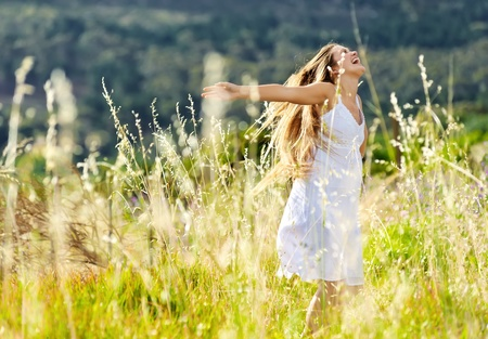 beautiful girl laughs and dances outdoors in a meadow durning sunset