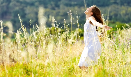 people dancing: beautiful girl laughs and dances outdoors in a meadow durning sunset
