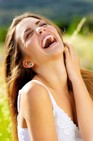 cute girl laughs with joy outdoors in the sunlight photo