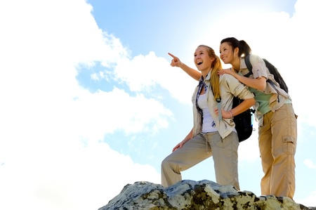 adventure holiday: two girls reach the summit of a climb and point out at the view