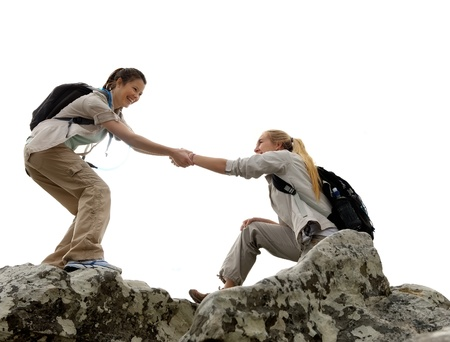 climbers: Hiker woman helps her friend climb up the last section of mountain. teamwork in outdoor lifestyle adventure