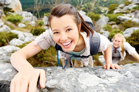 climbing: happy woman climbs a rock while trekking outdoors. carefree backpacker smiling at camera