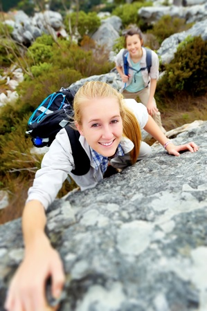 happy woman climbs a rock while trekking outdoors. carefree backpacker smiling at camera Stock Photo - 11474445