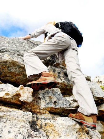 hiking shoes: woman climbing rock face, view from bottom with selective focus on hiking boot