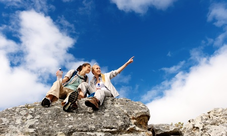 admire: hikers take a break, sit on a rock and admire the view. the blonde girl points off into the distance Stock Photo