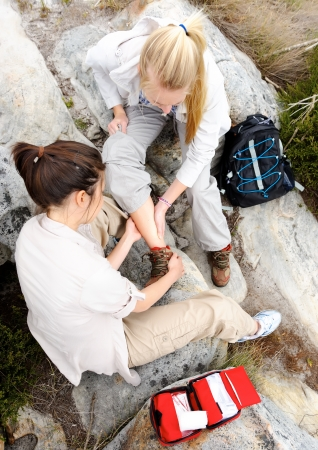sprain: hiker with sprained ankle is helped by her friend with first aid kit for outdoor emergency