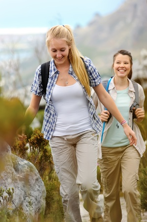 backpacking: two young woman go hiking outdoors and smile as they walk