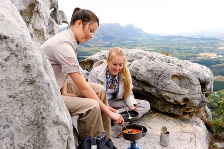 vista: two woman cook some hiking food on a gas stove while sitting on top of a mountain Stock Photo