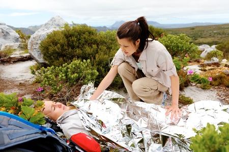 primeros auxilios: Médica de emergencia durante una excursión. mujer tiene manta de emergencia y que su amiga está pidiendo ayuda