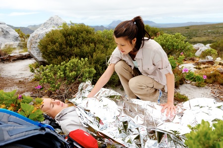 first help: Medical emergency while hiking. woman has emergency blanket and her friend is calling for help
