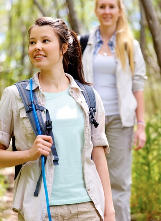 two beautiful attractive woman hiking outdoors in the woods. healthy active lifestyle concept Stock Photo - 11474455