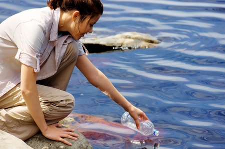 refills: woman refills her empty water bottle in a clear mountain lake while on her outdoor hike in nature
