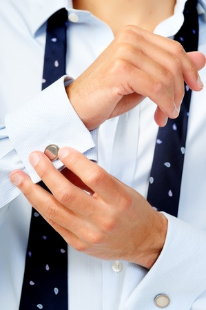 Anonymous caucasian man adjusts his cufflinks while dressing himself for work Stock Photo - 11598387