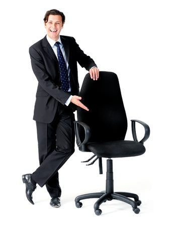 Happy businessman gestures to an empty seat, a recruitment concept  photo
