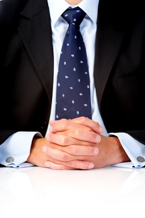the well groomed: Anonymous portrait of a man in a business suit sitting at a table with his hands clasped together