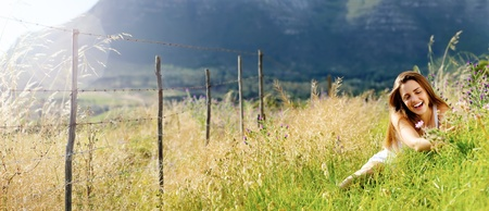 carefree vitality woman is happy outdoor in a field.  large panorama image with copyspace. photo