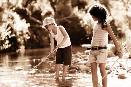 Children fishing in a river, nostalgic aged sepia tone Stock Photo - 11598502