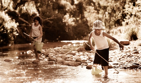 Children fishing in a river, nostalgic aged sepia tone photo