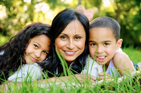 lifestyle home: Happy family outsoors on the grass in a park, smiling faces all lying down having fun Stock Photo