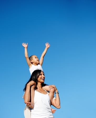 young boy sits on his moms shoulders and reaches for the sky photo