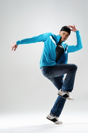 cool modern breakdancer warming up in studio, photo