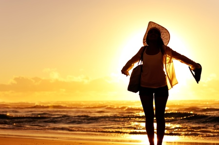 carefree woman dancing in the sunset on the beach. vacation vitality healthy living concept photo