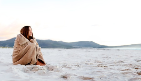 cold woman wraps blanket over hersolf while sitting on the beach after sunset. copyspace provided by panoramic image Stock Photo - 11900243