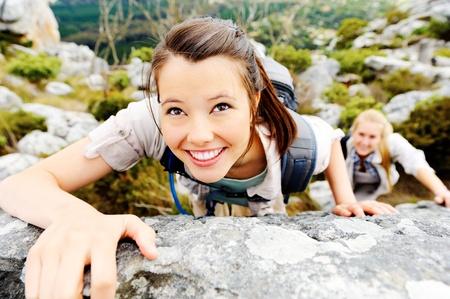 escalando: mochileros feliz caminata despreocupada sube a la intemperie de rock, mientras que lleva un estilo de vida saludable Foto de archivo