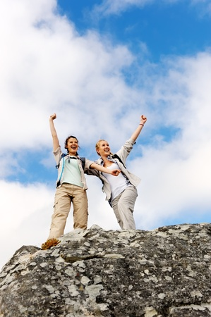 happy hiking women have made it to the summit and they raise their arms up in joy photo