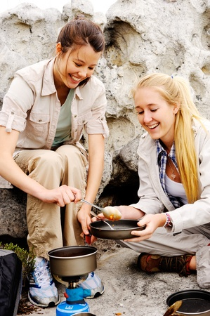 two friendly women cook up some food while camping in the wilderness. outdoor hiking lifestyle concept photo
