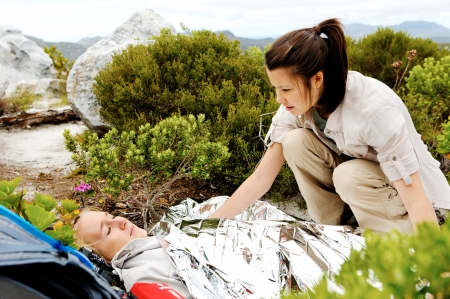 A woman is injured while hiking outdoors. her friend has covered her with and emergency blanket and checks on her using a first aid kit